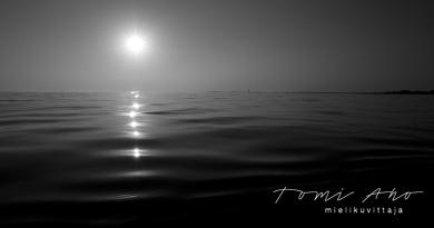 Meri heijastelee helmeilevästi Ahvenanmaan mantereen äärellä. tummasävyinen maisemakuva on kuvattu iltapäivällä kajakista.