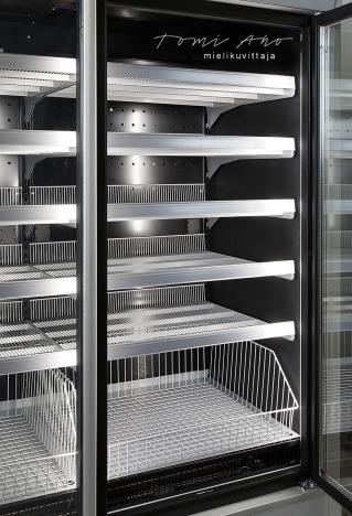 Kylmäkaapissa on monta hyllyä tuotteita varten ja se on hyvin valaistu sekä tyylikäs.