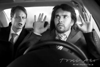 mies nostaa kädet auton ratista ja takapenkillä istuva mies hämmästelee tilannetta. mies ei suostu ajamaan, ennen kuin takapenkillä oleva mies laittaa turvavyön kiinni © Studio Tomi Aho mielikuvittaja