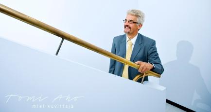 harmaahiuksinen silmälasipäinen mies hymyilee portaikossa. kullanvärinen kaide halkoo kuva, joka on kauttaaltaan sinisävyinen.