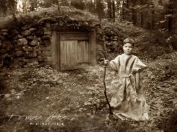 pieni poika seisoo maakellarin edessä juuttikangas-asussa keppi kädessään