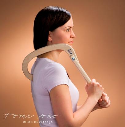 nainen hieroo kipukoukulla yläselkää. tummahiuksinen nainen on asettanut kipukoukun selkänsä kipeään kohtaan ja hieroo sitä pitämällä kipukoukusta kaksin käsin kiinni.