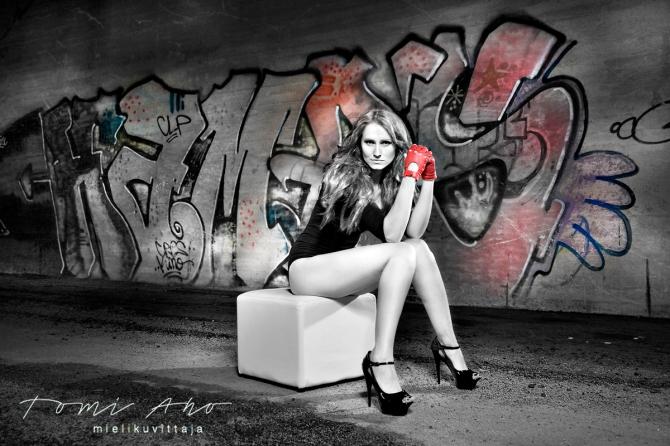 nainen istuu graffitin äärellä sillan alla. naisella on punaiset ajohanskat ja päällään body, hän istuu valkoisella jakkaralla.