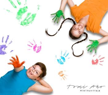 tyttö ja poika makaavat valkoisella lattialla johon on painettu kädenjälkiä eri väreillä. lapset hymyilevät ja ovat innoissaan sormiväreistä, joilla he ovat painaneet kätensä kuvia valkoiseen lattiaan.