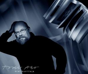 Finnfoto palkinnon saaja Jukka Kukkonen muotokuvassa. Tietokirjailija Jukka Kukkonen Tomi Ahon kuvaamassa ja käsittelemässä muotokuvassa. Kukkonen nojaa seinään, kirja leijuu ilmassa.