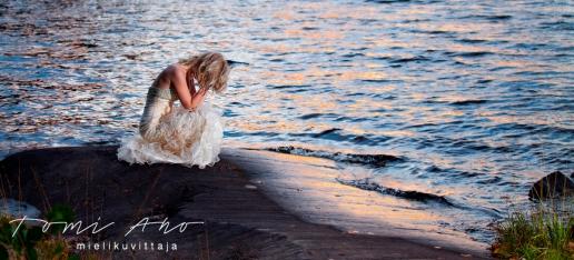 tyttö kalliolla ilta-auringossa. tyttö on painanut päänsä kyykistyneenä valkoisessa mekossaan sileällä kalliolla, joka heijastaa vettä ja taivasta.