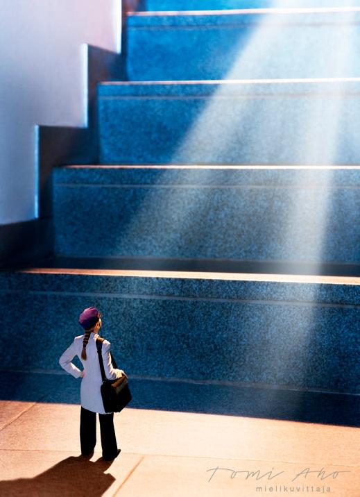 lakkipäinen lettipäinen nainen katsoo valtavien portaiden myötäisesti ylös, josta säteilee valo. uuden insinööriliiton mainoskampanjakuva, miten työllistyä kouluttautumisen jälkeen.