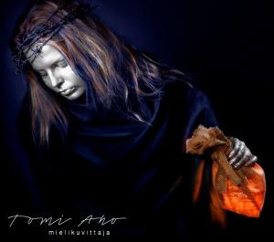 hopeakasvoinen nainen kannattelee kädessään juuttikankaista pussukkaa, joka säteilee valoa. naisen päässä on piikkilankaseppele ja hän kantaa kädessään valoa