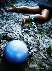 Nainen makaa hiekalla, metallipallo on kiinni paksulla kettingillä jalassa © Studio Tomi Aho mielikuvittaja
